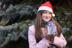 Girl with present in Christmas hat Royalty Free Stock Image