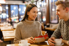 Girl with present. Happy couple sitting in cafe on xmas evening Royalty Free Stock Images
