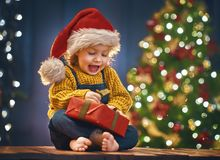 Girl with present. Merry Christmas and Happy Holiday! Cute little child girl with present gift box near tree at home Stock Image