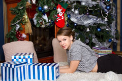 Girl with present near the Christmas tree Stock Images