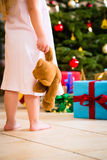 Girl with present and teddy on Christmas day Stock Images