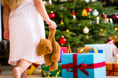 Girl with present and teddy on Christmas day Stock Photos