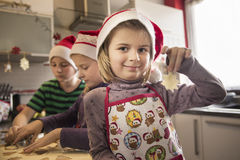 A girl presenting a Christmas cookie in a kitchen stock photos
