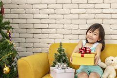 The girl is presenting a Christmas gift. girl showing the gift box. Cute asian kid holding a Christmas box. happy new year. Merry stock photos