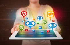 Girl presenting a tablet with colorful social icons and signs Royalty Free Stock Images