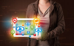 Girl presenting a tablet with colorful social icons and signs Stock Image