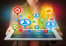 Girl presenting a tablet with colorful social icons and signs Stock Photo