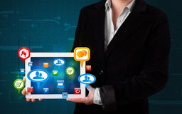 Girl presenting a tablet with colorful social icons and signs Royalty Free Stock Photo
