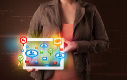 Girl presenting a tablet with colorful social icons and signs Stock Photos