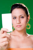 Girl presenting white card. Beautiful girl presenting white card on green background Royalty Free Stock Images