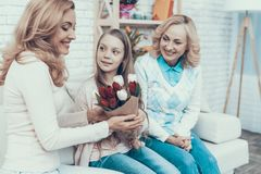 Girl Presents Bouquet of Tulips to Smiling Mother stock photo