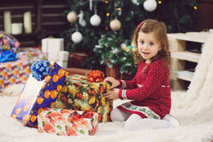 Girl with Presents at Christmas Tree Royalty Free Stock Photography