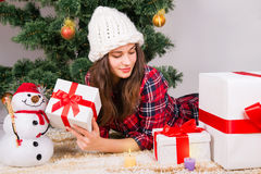 Girl with presents under the Christmas tree. Smiling girl with presents under the Christmas tree Stock Image