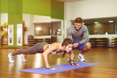 The girl pressed in  gym with  trainer. Fitness, girl pushed in the gym under the supervision of a trainer. The concept of Health, sports Stock Photography