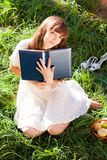 Girl pressed her book and smiles dreamily Stock Photo