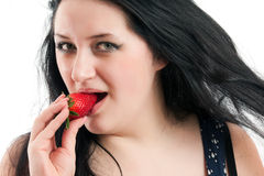 The girl presses a strawberry to the lips Royalty Free Stock Images