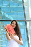 Girl presses to herself a slice of watermelon. On a background of the glass facade of the building Royalty Free Stock Images