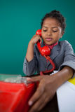 Girl pretending as businesswoman talking on land line phone. While sitting at desk against blue background Royalty Free Stock Photos