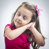 Girl pretending she is sleeping. Four years old girl pretending she is sleeping on a studio shooting Royalty Free Stock Images
