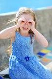 A girl pretending to be looking through binoculars Royalty Free Stock Photography