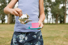 Girl pretending to pour tea Stock Photo
