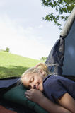 Girl Pretending To Sleep In Tent. Closeup of a girl pretending to sleep with a smile in the tent Stock Photography
