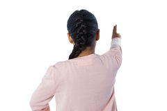 Girl pretending to touch an invisible screen against white background Royalty Free Stock Photography