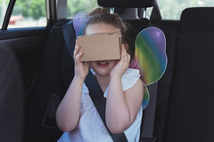 Girl pretending to use virtual reality headset. In car Stock Photo