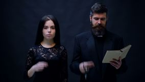 The girl and priest are baptized on a black background. Halloween party and celebration concept. stock video footage