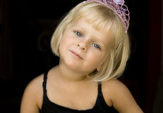 Girl with princess crown. A 4 year old  blond little girl with a pink tiara. Isolated on black Stock Image