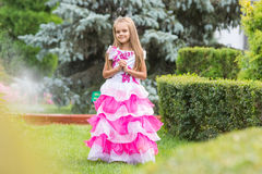 Girl princess stands on the lawn in the green garden Royalty Free Stock Images