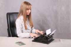Girl printing on the typewriter Royalty Free Stock Photography