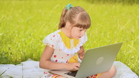 Girl prints on a laptop in a meadow stock video footage