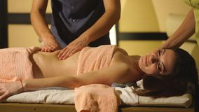 Girl on the procedure for four hands massage in the spa salon stock footage