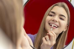 Girl on the procedure of teeth whitening checks the color tone of the teeth royalty free stock image