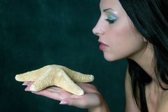 Girl in profile with starfish Stock Photos