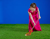 Girl in prom dress playing with lacrosse stick. High school girls lacrosse player scooping up the ball with her lacrosse stick while wearing a bright pink prom Stock Image