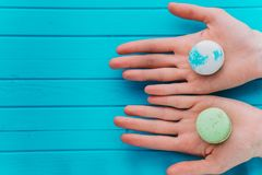 Girl proposes macaroons or macarons on a turquoise background. Top view, copy space.  Royalty Free Stock Image