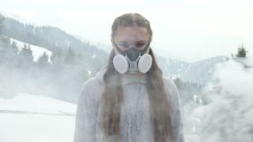 Girl is protected from bad air and smoke in a gas mask. The girl is protected from bad air and smoke in a gas mask stock video footage