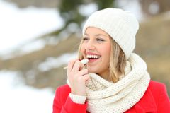 Girl protecting lips with lip balm in winter. With a snowy mountain in the background royalty free stock photo