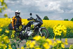 Girl in a protection outfit and glasses with touristic motorcycle. Rape yellow flowers field on background. Adventure trail tour, stock images