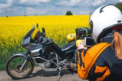 Girl in a protection outfit and glasses with touristic motorcycle. yellow flowers field. Adventure trail tour, enduro and off road royalty free stock photos