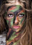 Girl in protective camouflage. With military makeup on her face Stock Images