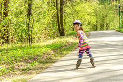 Girl in protective equipment and rollers in park, outdoor Royalty Free Stock Photos