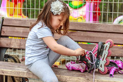 Girl in protective equipment and rollers in park, outdoor Stock Image