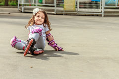 Girl in protective equipment and rollers in park, outdoor Stock Photos