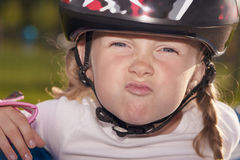 Girl in protective helmet making grimace   outside Stock Photo