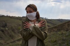 Girl in protective mask against the coronavirus on landscape background, COVID-19, funny and smiles