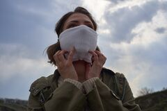 Girl in protective mask against the coronavirus on landscape background, COVID-19, stop