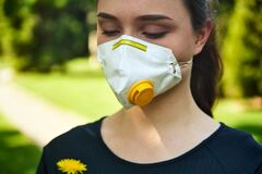 Girl in a protective mask smiles with dandelion in hand, COVID-19 coronavirus prevention, nature protection, quarantine time